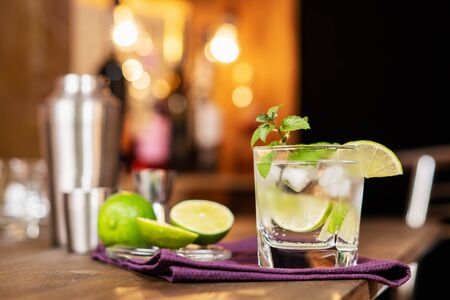 Lime cocktail with mint and ice on the background of the bar. Refreshing alcoholic cocktail.