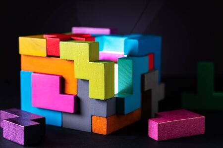 Cube made of multicolored wooden geometric shapes. Concept of decision making process, creative, logical thinking. Choose correct answer. Logical tasks. Conundrum, find the missing piece of the proposed. Reklamní fotografie - 139756064