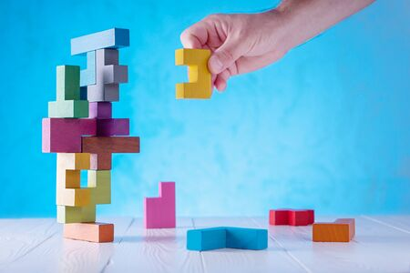 Concept of decision making process, logical thinking. Logical tasks. Conundrum, find the missing piece of the proposed. Hand holding wooden puzzle element.