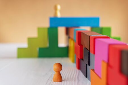 Abstract man standing in front of a wall or barrier of multicolored wooden blocks. Business concept. Reklamní fotografie