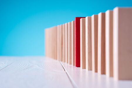 Red wooden block in a row of colorless blocks. Stand out from the crowd and different thinking concept. The concept of uniqueness, distinction from others.