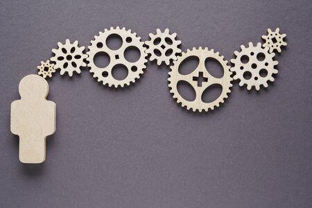 Homme abstrait avec des engrenages sur fond gris - concepts d'entreprise, fonctionnement, efficacité, pièces imbriquées.
