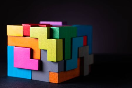 Cube made of multicolored wooden geometric shapes. Concept of decision making process, creative, logical thinking. Choose correct answer. Logical tasks. Conundrum. Reklamní fotografie