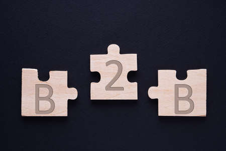 Three jigsaw puzzle pieces with B2B. Business to Business concept.