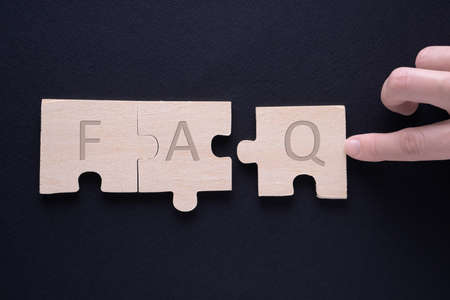 Hand attaches the missing piece of the puzzle. FAQ word on wooden cubes.