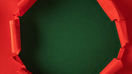 Red paper is torn over green background for message. Template for your text. Reklamní fotografie