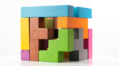 Cube made of multicolored wooden figures on a white background. Concept of logical thinking.