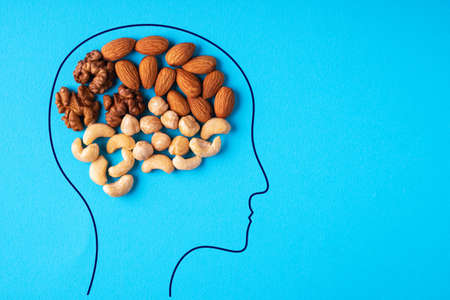 Head with nuts of abstract brain on blue background.