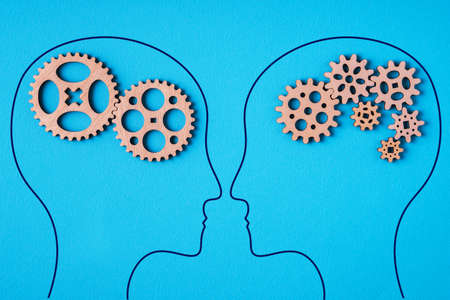 Heads of two people with a gear mechanism in the head. Two people with different thinking.