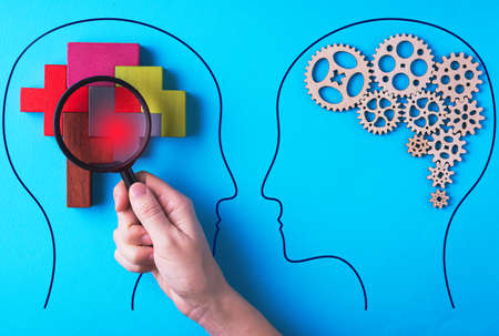 Human brain is made gear mechanism and colorful shapes on blue background. The brain is viewed through a magnifying glass. Brain disturbance concept, brain disorder. Different thinking. Reklamní fotografie