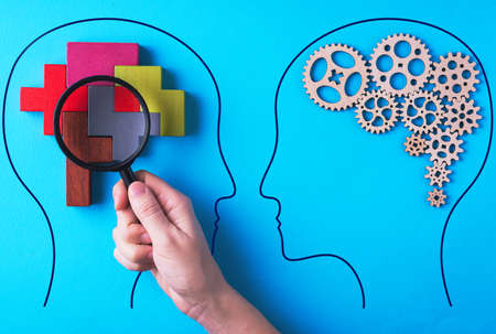 Human brain is made gear mechanism and colorful shapes on blue background. The brain is viewed through a magnifying glass. Two different thought processes, concept of different thinking.