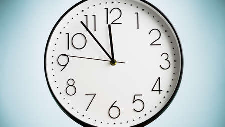 Analog white wall clock on green background. Clock in closeup. Time concept.