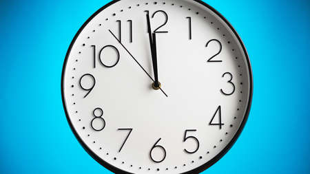 Analog white wall clock on blue background. One minute to twelve. Clock in closeup. Time concept.