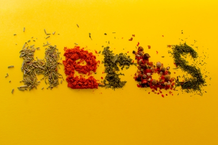 Assorted herbs spelling the word herbs, isolated on a yellow background  photo