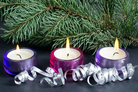 christmas tree branch with three burning candle and ribbon over black background  Stock Photo - 16272163