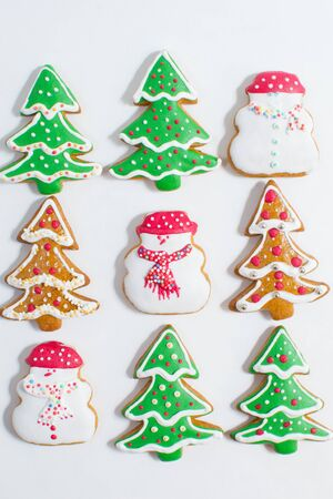 Christmas gingerbread cookie made in the shape of a Christmas trees and snow man isolated on a white background  photo