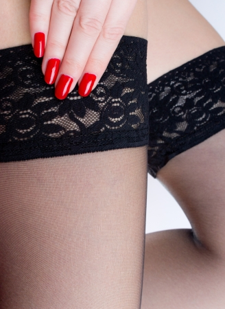 Sexy female legs in black stockings and red nails Stock Photo - 18819259
