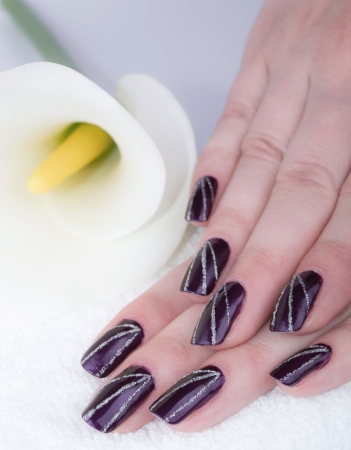 Woman with beautifully manicured purple nails with cala lily photo