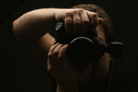macro photography: Photographer with camera on black ground Stock Photo