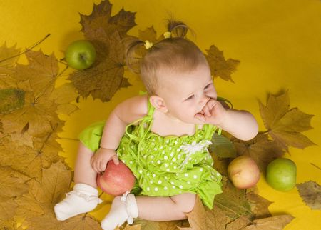 Baby with leaves and apples on yellow ground photo