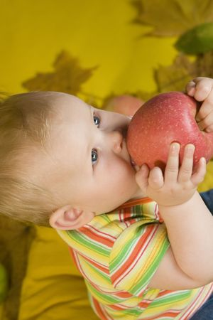 Baby eating apple on yellow ground photo