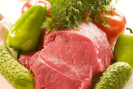 Raw meat with fresh vegetables photo