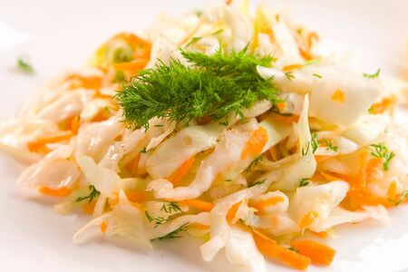 Coleslaw decorated with dill on white plate