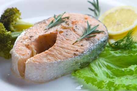 Salmon steak prepared on steam on white plate
