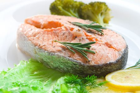 Prepared salmon steak with broccoli and lemon slices on white plate Stock Photo