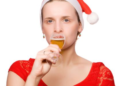 Young woman in christmas hat is drinking champagne on white ground photo