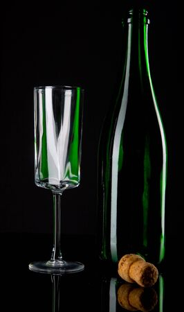 Bottle of champagne with glass on black ground photo