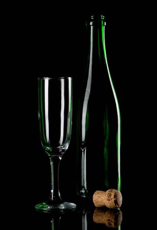 Champagne bottle with glass on black ground photo