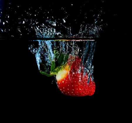 Strawberry in water with bubbles on black ground photo