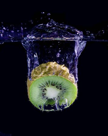 Kiwi  in water with bubbles on black ground photo