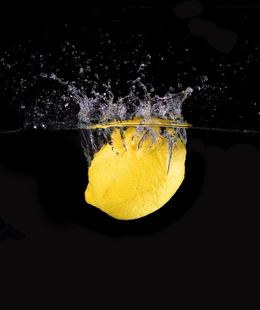 Lemon in water with bubbles on black ground