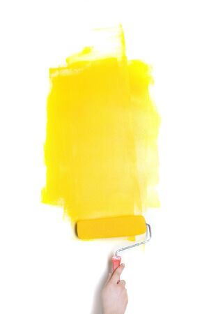 Paintig roller with yellow paint in human hand photo