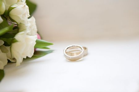 Two wedding rings and flowers Stock Photo