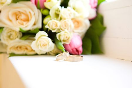 Two wedding rings behind flowers