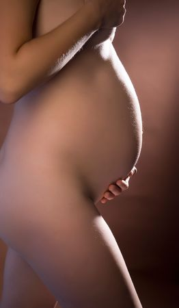 Young naked pregnant woman on brown ground Stock Photo - 5447252