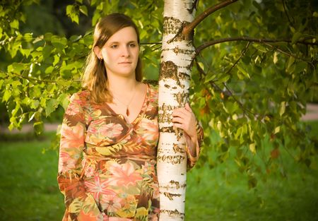 Pregnant young woman holding birch photo