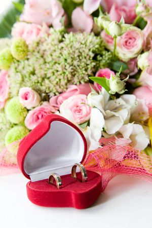 Two wedding rings in a box infront of flowers Stock Photo
