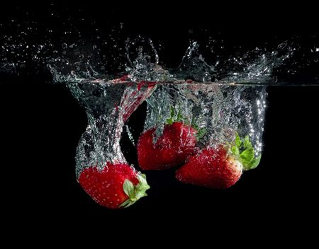 strawberry splash: strawberries in water with bubbles on black ground