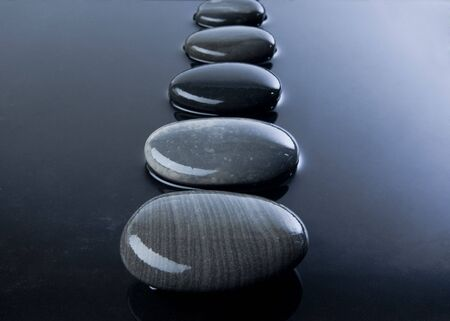 A row of shiny black pebbles in water Stock Photo - 6199723