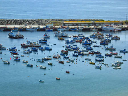 Small fishing boats docked in a small port in Sines, Portugal