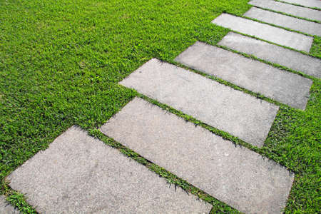 Detail of a pavement path going through the grass