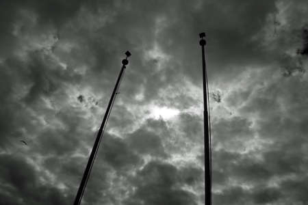 Dramatic dark sky full of clouds with sun reflection between two poles