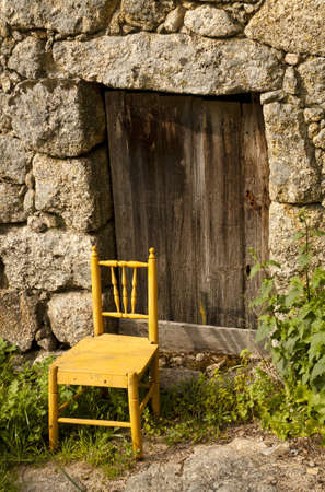 Door of an ancient house with a chair in the entrance photo