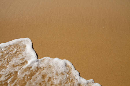 Wave over sand - with upper copy space