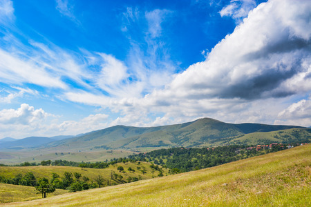mountains and sky: Abstract clouds forming over Zlatibor mountain. Grassland in front.