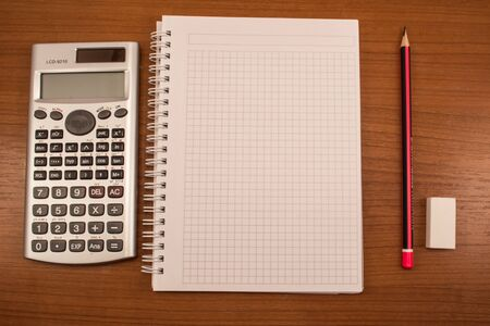 pencil eraser: Calculator, pencil, eraser and notebook on the wooden table